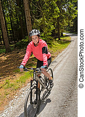 Woman mountain biking in sunny forest smiling - Woman...