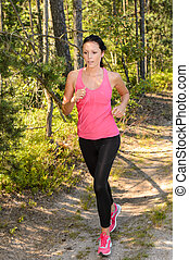 Athlete woman running through forest training in the...