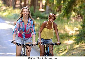 Two teenage girls riding their bikes