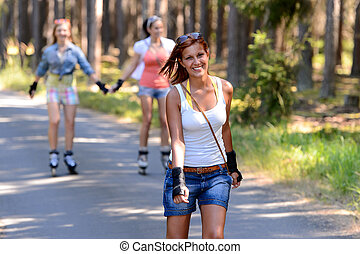 Young woman roller skating outdoors with friends summer...
