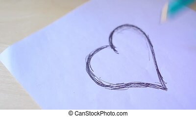 Drawing heart on a piece of paper.