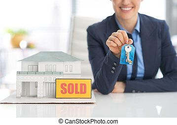 Closeup on happy realtor woman showing keys