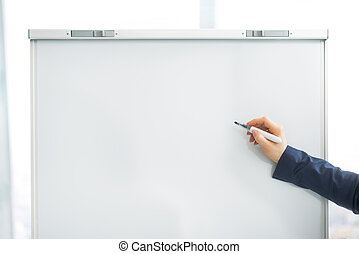 Closeup on business woman writing on flipchart