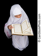 Young Girl Reading Al Quran - Young Asian Muslim girl in...
