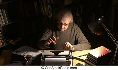 Writer at work - An elderly man typing his creation on...