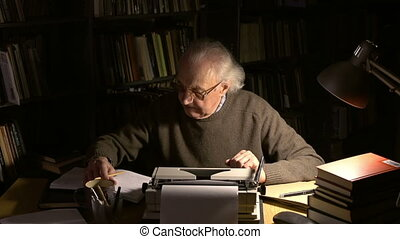 The main point - A mature man sitting at the desk, typing on...
