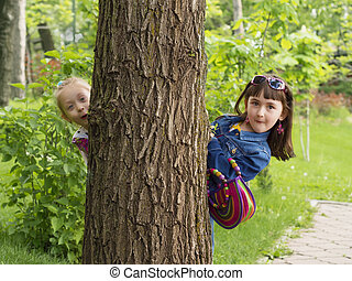 Girls surprize - Two girls peeking from a tree