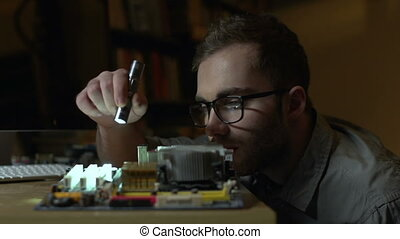 Disassembling system board - A man wearing eyeglasses with a...