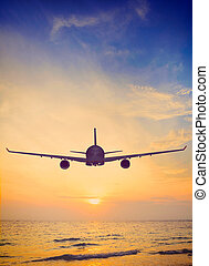 sunset airplane - airplane is flying over the sea at sunset