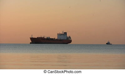 tug and tanker - tugboat and oil tanker at sunrise