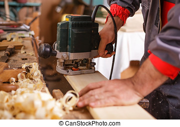 Carpenter at work with electric planer joinery - The...