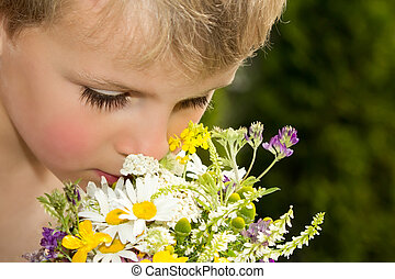 Young Boy Smelling Bouquet of Wildflowers picked with his...