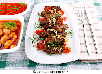 Grilled cevapcici with ajvar and giant white beans, close up