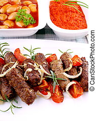 Grilled cevapcici with giant white beans and ajvar, close up