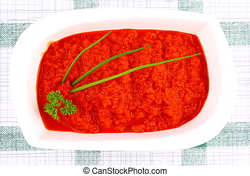Bright red ajvar in white bowl with parsley, spring onion,...