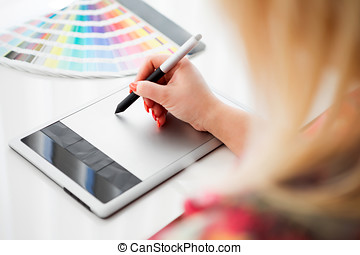Graphic designer working on a digital tablet in the...
