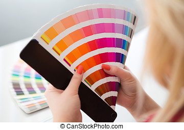 Graphic designer working with pantone palette in studio
