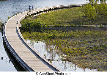 Bicycling on boardwalk - Bicyclists are riding along the...