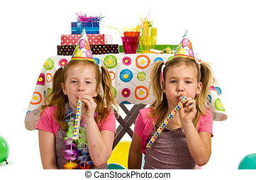 Girls with party blowers on a birthday party
