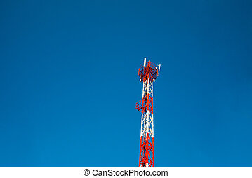 A red white telecommunication tower under the blue sky