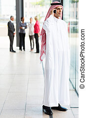 muslim businessman in traditional clothes talking on cell...