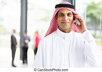 arabian businessman talking on cell phone - smiling arabian...