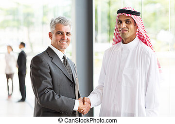 senior businessman handshake with Arabian partner -...