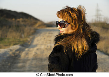 Girl with red hair and big sun glasses in the field road -...