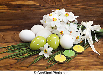 Easter eggs and white daffodils on wooden background