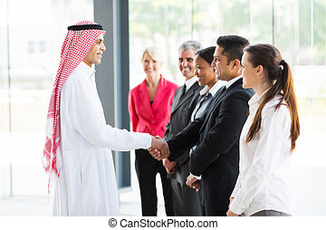 Arabian businessman handshaking with his employees