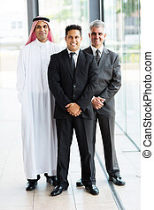 group of multicultural businessmen standing in modern office