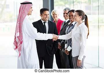 group of businesspeople welcoming Islamic businessman -...