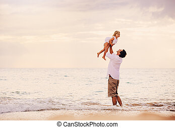 Father and Daughter Playing Together at the Beach at Sunset...