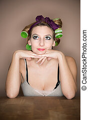 musing thoughtful girl with hair curler at table