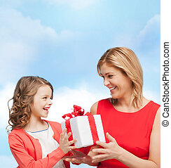 smiling mother and daughter with gift box - family, child,...