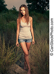 Female with crossed legs outdoors toned image