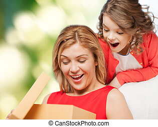 smiling mother and daughter opening gift box - family,...