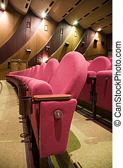 Cinema interior - Pink row 1 of empty cinema auditorium with...