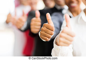 business people giving thumbs up - closeup portrait of...