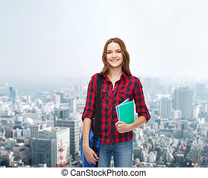 smiling female student with bag and notebooks - education...