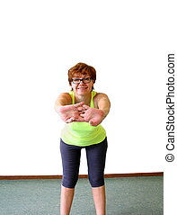 Mature, nice woman in yellow shirt doing fitness, isolated