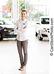 saleswoman standing at car dealership - attractive...