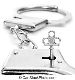 handcuffs - closeup of a pair of handcuffs with a key on a...