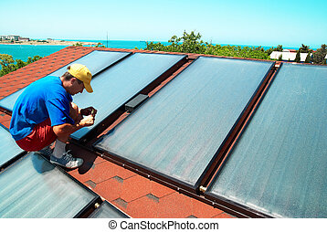 Worker installs solar panels - Worker mounting solar water...
