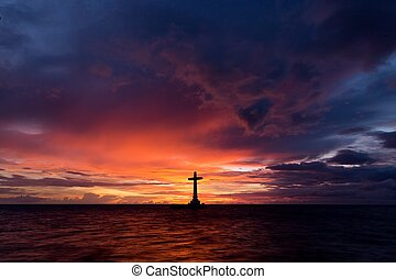 Catholic cross silhouette in a sunken cemetery at dusk,...