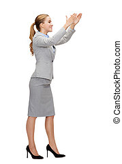 smiling businesswoman holding something imaginary - business...
