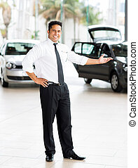 indian car salesman presenting new cars - good looking...