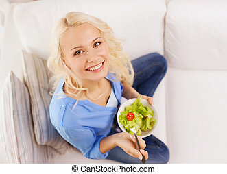 smiling young woman with green salad at home - healt,...