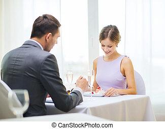 smiling couple eating dessert at restaurant - restaurant,...