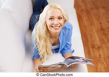 woman lying on couch and reading magazine at home - home and...